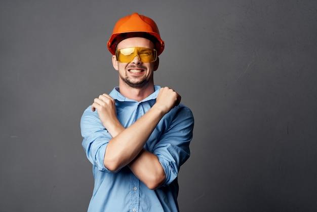 Веселый человек в оранжевой каске строительных профессиональных инструментов