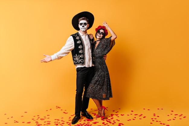 ソンブレロの陽気な男とハロウィーンの化粧をした彼のエレガントな女性は、オレンジ色の壁に抱き締めて、楽しくポーズをとっています。