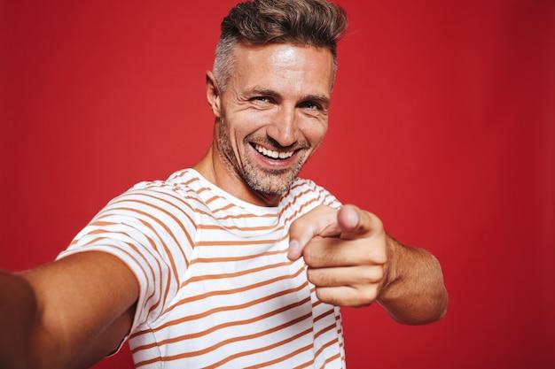 Жизнерадостный мужчина в полосатой футболке улыбается и показывает пальцем на вас, делая селфи на красном