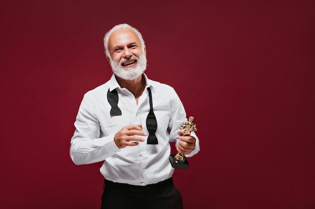 세련된 의상을 입은 쾌활한 남자가 샴페인으로 수상을 축하합니다.