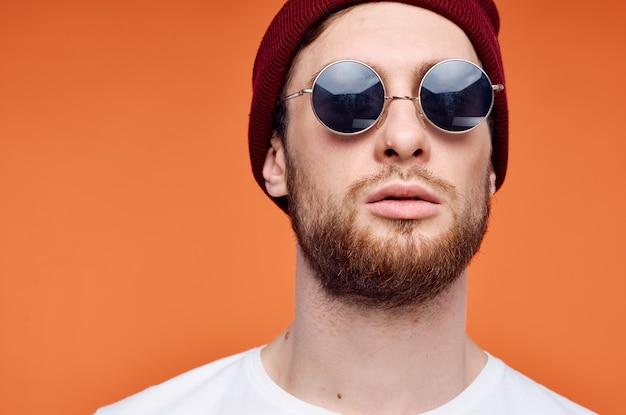 花オレンジ色の背景を保持しているサングラスの陽気な男