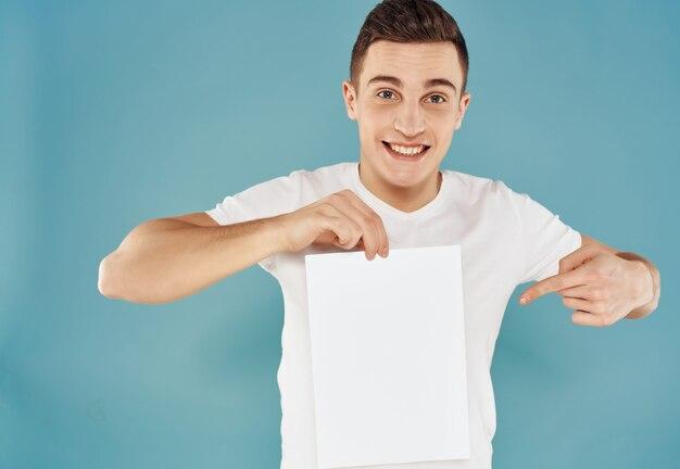 紙のコピースペーススタジオ孤立した背景のシートと白いtシャツの陽気な男