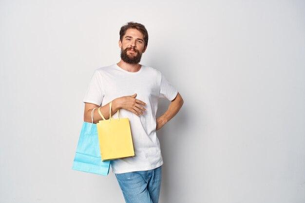 쇼핑 감정 라이프 스타일의 팩과 흰색 티셔츠에 쾌활 한 남자