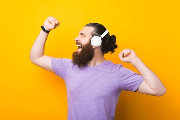 陽気な男は黄色の背景の上で踊って音楽を聴いています。
