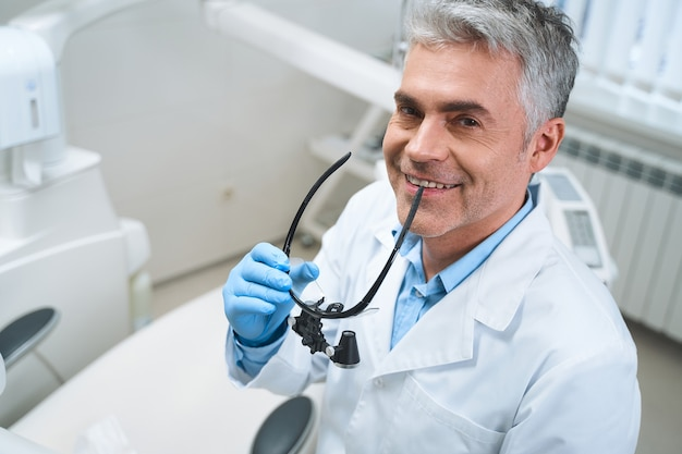 Cheerful man is medical uniform is enjoying his work with patients and holding professional glasses in hends