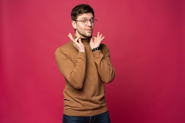 Веселый человек смеется и смотрит в камеру. портрет счастливого молодого человека, стоящего на розовом фоне.