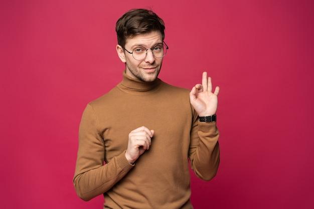 笑って直接見ている陽気な男。ピンクの背景の上に立っている幸せな若い男の肖像画。