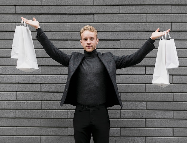 Cheerful man lifting up the shopping bags