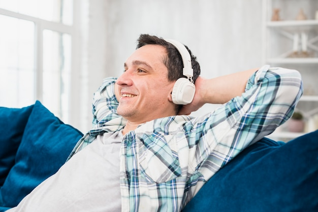 Cheerful man listening music in headphones on sofa