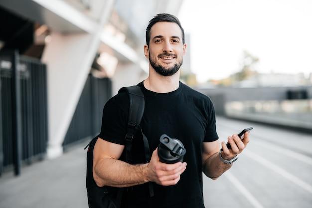 카메라를 보고 웃 고 쾌활 한 남자입니다. 스포츠 병과 스마트폰을 손에 들고 검은 옷을 입은 젊은 남성 운동선수. 매력적인 남자가 함께 아침 달리기를 시작할 친구를 기다리고 있습니다.