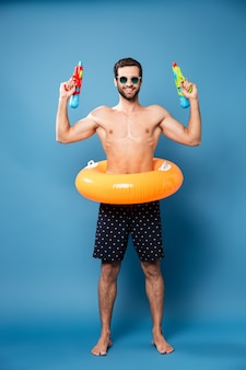 Cheerful man looking camera while holding water guns isolated