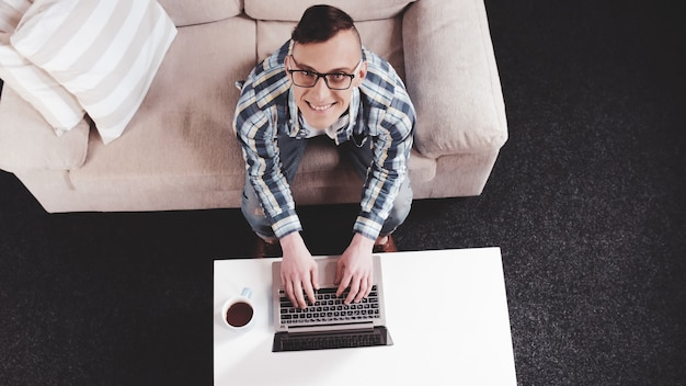 Cheerful man looking up typing on laptop