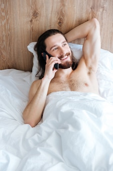 Cheerful man lying in bed and talking on cell phone