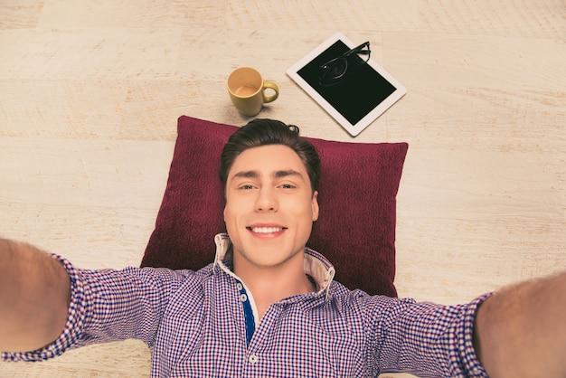 枕の上で床に横たわって自分撮りをしている陽気な男