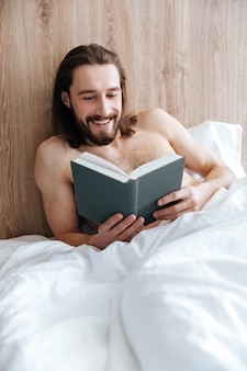 Cheerful man lying and reading book in bed