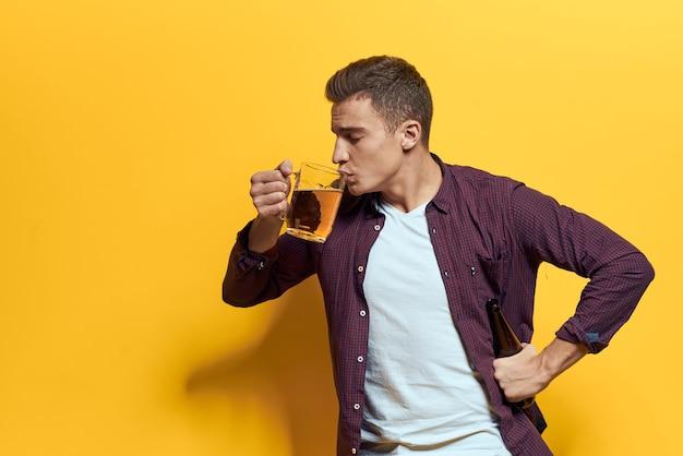 Веселый мужчина кружка пива с бутылкой весело пьяный образ жизни алкогольный желтый.