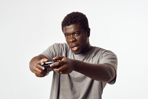 彼の手にジョイスティックを持つアフリカの外観の陽気な男は、ビデオゲームをプレイします