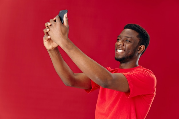 アフリカの外見の陽気な男性が携帯電話を手に持ち、ビュー技術をトリミング