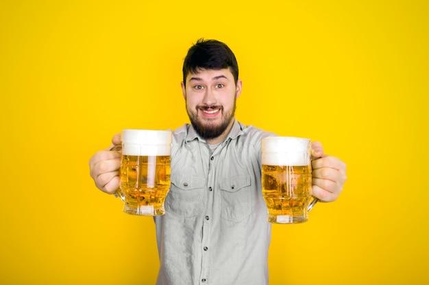 쾌활한 남자는 뷰어에게 맥주 잔, 노란색 벽 위에 이미지를 제공합니다.