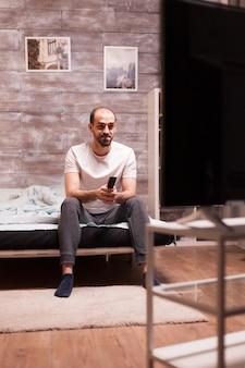 Uomo allegro in pigiama di notte guardando la tv tenendo il telecomando.