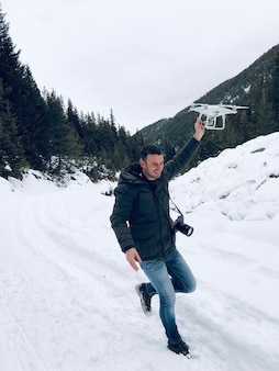 Веселый человек-фотограф летит с дроном во время путешествия в зимние горы