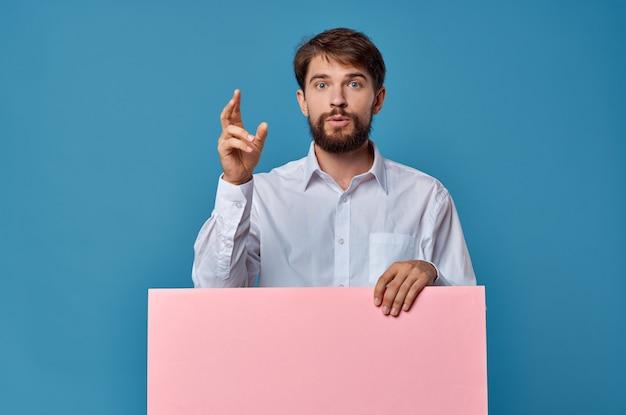 明るい男ピンクのバナーを手に空白のシートプレゼンテーション青い背景