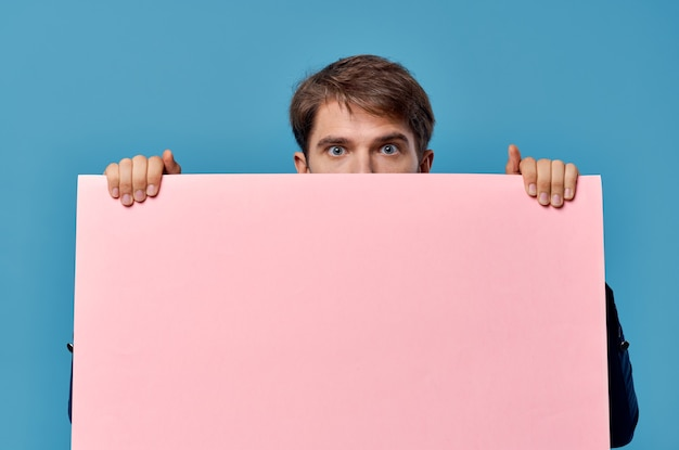 マーケティングの楽しいライフスタイルの青い背景の手に陽気な男のピンクの紙