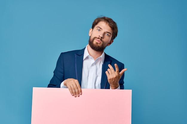 マーケティングの楽しいライフスタイルの孤立した背景の手に陽気な男のピンクの紙