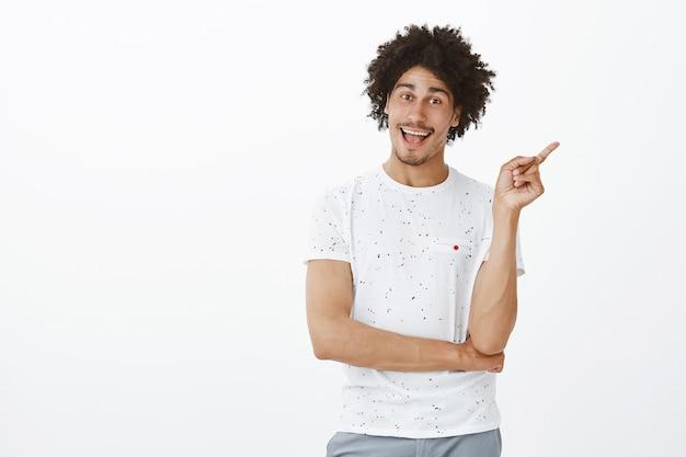 Веселый человек указывает пальцем вправо и говорит нажать на баннер или показ рекламы