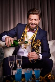シャンパンのシャンパンフルートを注ぐ陽気な男