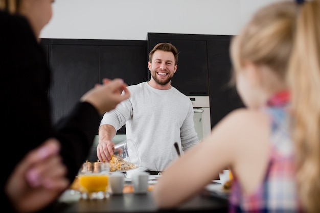 Cheerful man preparing breakfast for family