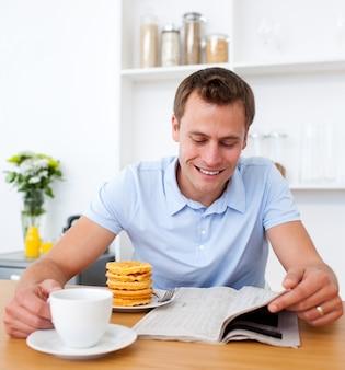 朝食をしながら新聞を読んでいる明るい男