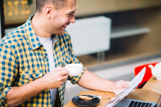 新聞を読んでコーヒーを持っている明るい男