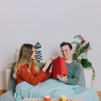 Cheerful man receiving gift from woman