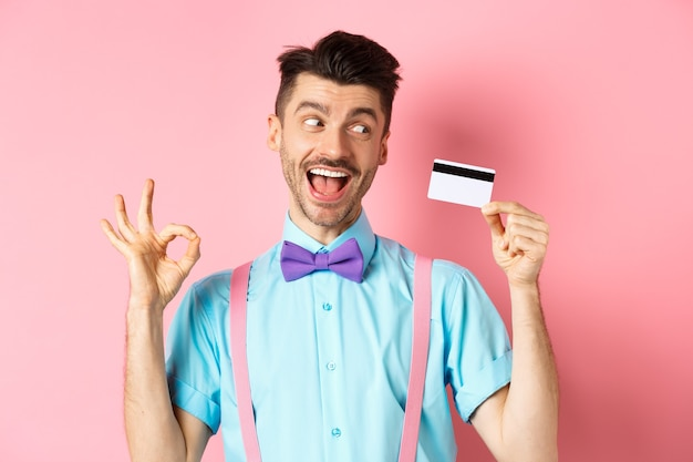좋은 프로 모션을 추천하고 확인 서명을 표시하고 분홍색 배경에 서있는 플라스틱 신용 카드에 흥분을 찾고 쾌활한 남자.