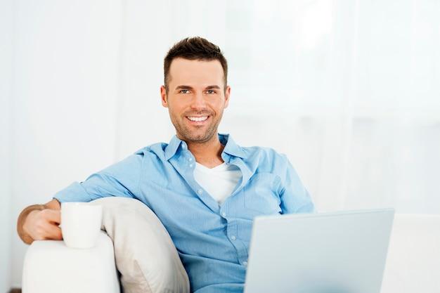 Uomo allegro che si distende con il computer portatile e la tazza di caffè