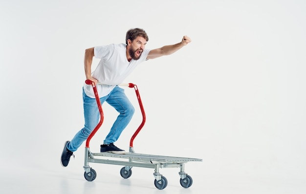 Cheerful man rides on a cargo cart in a bright room