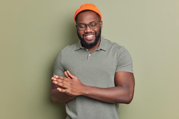쾌활한 남자는 손바닥을 문지른다. 치아가 기쁨에서 눈을 감고도 기쁨에서 눈을 감고도 행복한 표정을 지었다. 유쾌한 소식은 주황색 모자를 쓰고 캐주얼 티셔츠를 실내에서 포즈를 취한다.