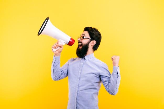 Веселый человек кричит в мегафон на желтом фоне