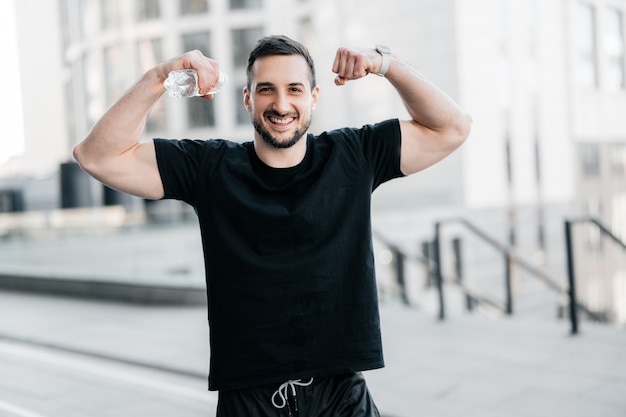 Cheerful man showing his muscles. hard workout concept. fit man showing biceps and smiling. gray morning city on background. handsome man excercised a lot to get a fit body.