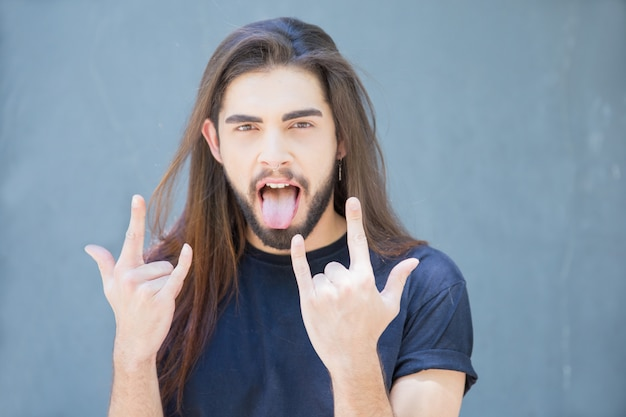 Cheerful man showing rock gesture to express success