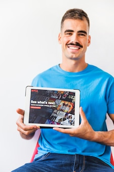 Cheerful man showing tablet with Netflix starting page