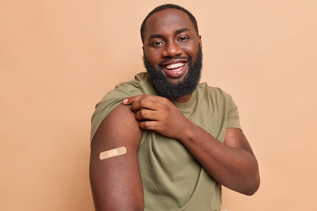 Cheerful man shows adhesive plaster on shoulder after getting coronavirus vaccine feels safe gets injection in arm cares about health during pandemic isolated over beige wall