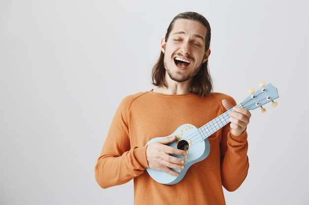 Cheerful man singing song and playing ukulele with happy expression