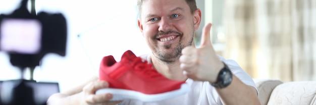 쾌활한 남자는 소파에 앉아 그의 손에 빨간 운동화를 들고 엄지 손가락을 보여줍니다. blogger는 집에서 동영상을 촬영합니다.