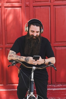 Cheerful man sitting on bicycle using mobile phone and headphones