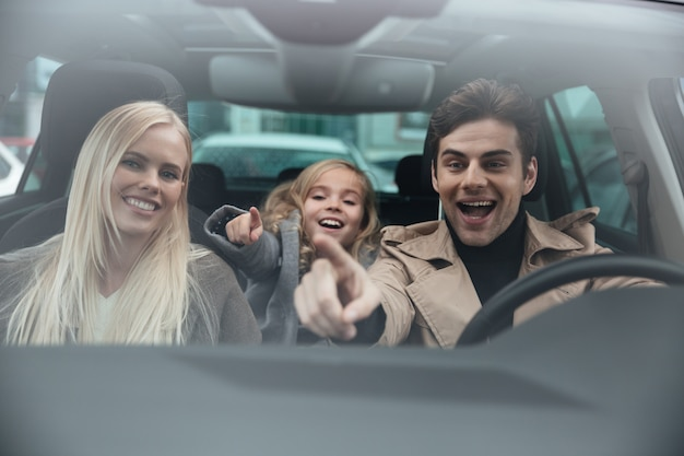 Cheerful man sitting in car with his wife and daughter
