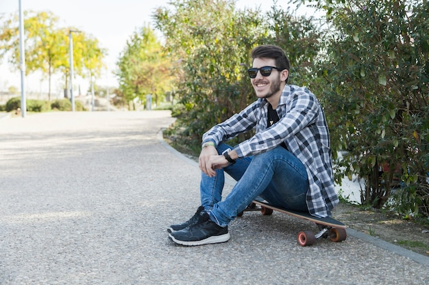 Веселый человек, сидящий на длинной доске