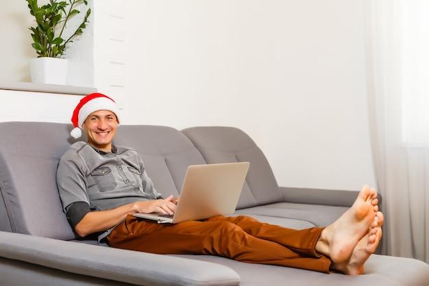 Веселый мужчина сидит на диване и пользуется ноутбуком возле елки дома