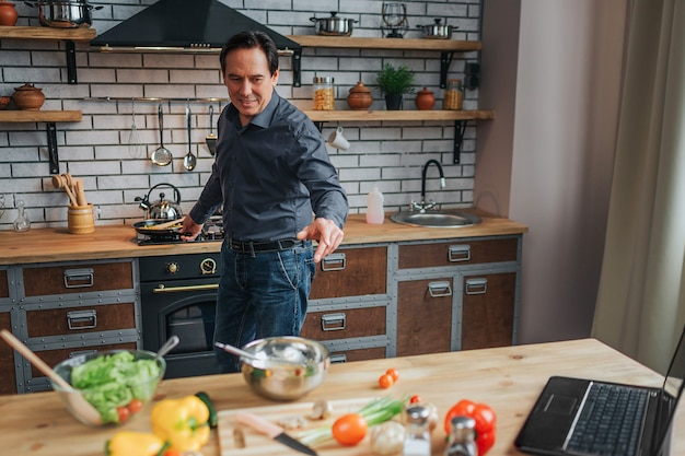 쾌활 한 남자는 스토브에 서서 부엌에서 음식을 요리합니다.